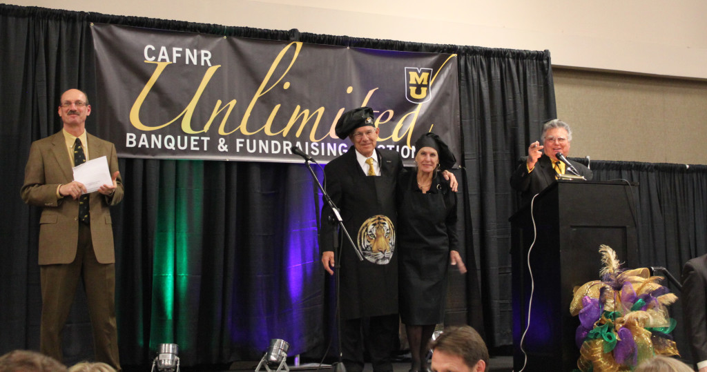 Dean Thomas Payne and wife, Alice, stand on stage during the auctioning of a dinner made by the couple.