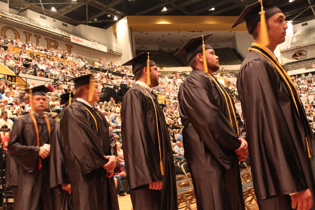 Students wait in line to cross the stage, receive their diplomas, and become alumni of the College.