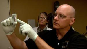 Jonathan Green, associate professor of animal sciences, examines an antibody-based test while William V. Stoecker looks on.
