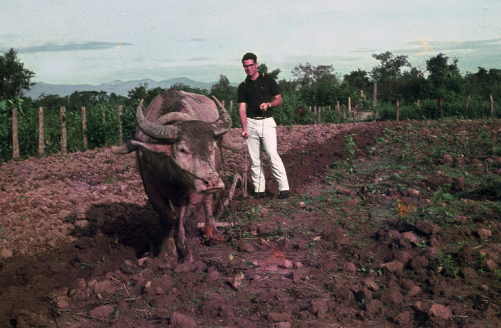 Deaton plows the soil in one of his school's research plots in Thailand.