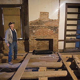 Ray Glendening observes the interior the house being restored. Note the trees that were used whole under the floor.