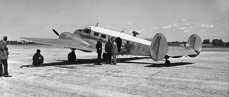 Mizzou's second airplane was a navigational trainer rebuilt to corporate configuration. AF-645 is seen here boarding passengers on the ramp of Columbia Municipal Airport, now Cosmo Park. Courtesy University Archives.