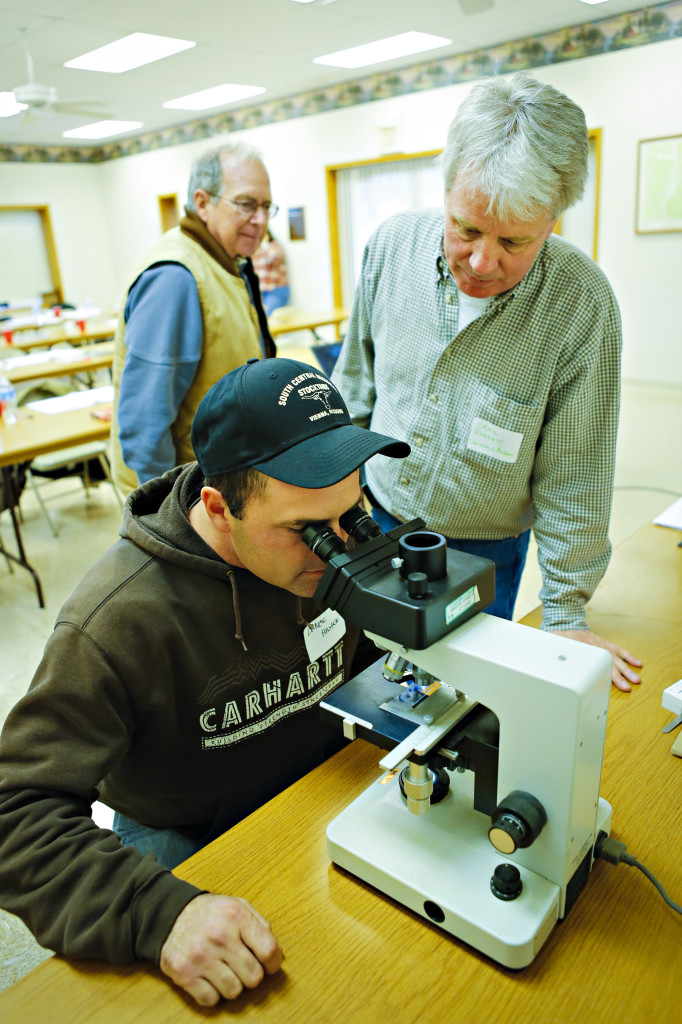 Craig Roberts, professor of plant sciences, shows Lance Hasten what novel endophytes look like through a microscope.