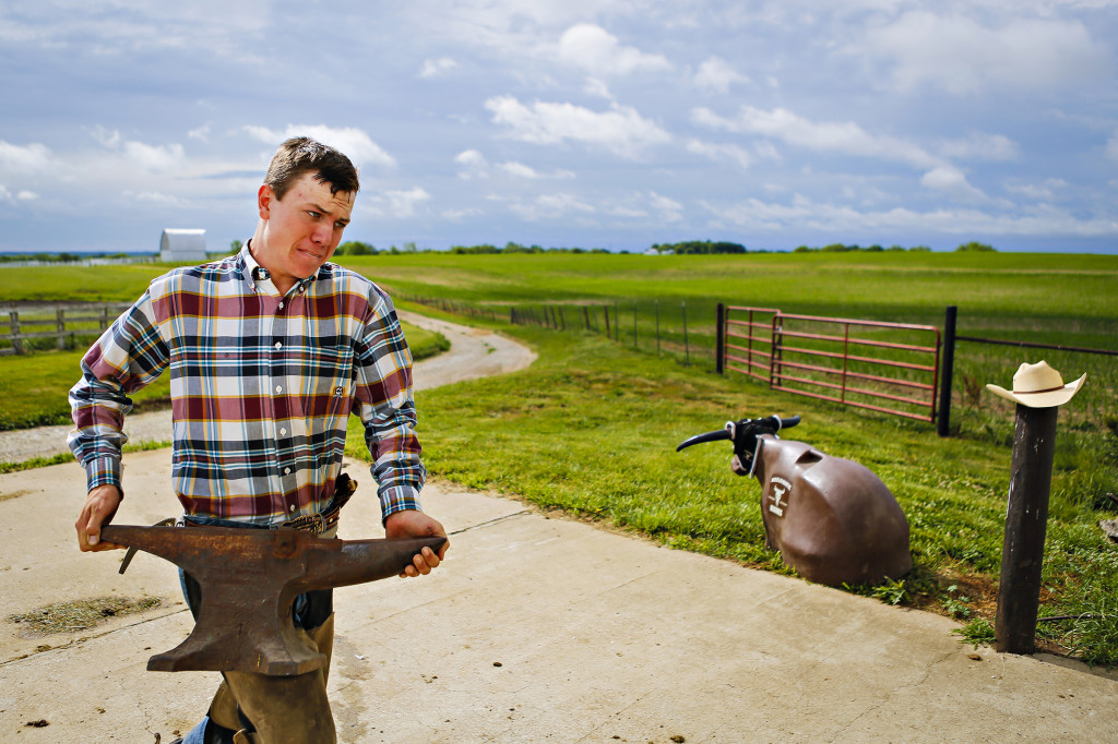 Zane carries an anvil from his truck to the horse arena. He uses the timeless tool to help reshape and fix horseshoes.