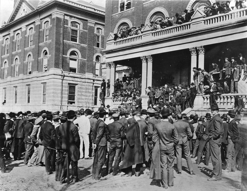 President Richard Jesse, unaware of the first Farmers' Week, met agriculture students wearing work clothes in the hallway outside of MU's chapel and would not permit them inside. The students gathered on the south steps of Jesse Hall, where Jesse (the bearded figure with his arm raised in the right center of the picture) chastised them for their disrespectful attire and ordered them to disband. They did and then paraded downtown with every available farm implement. Courtesy Mizzou Alumni Association.