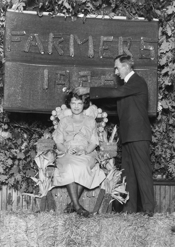 Dean Mumford crowns Farmers' Week Queen 1920 on a throne of corn. Courtesy University Archives.