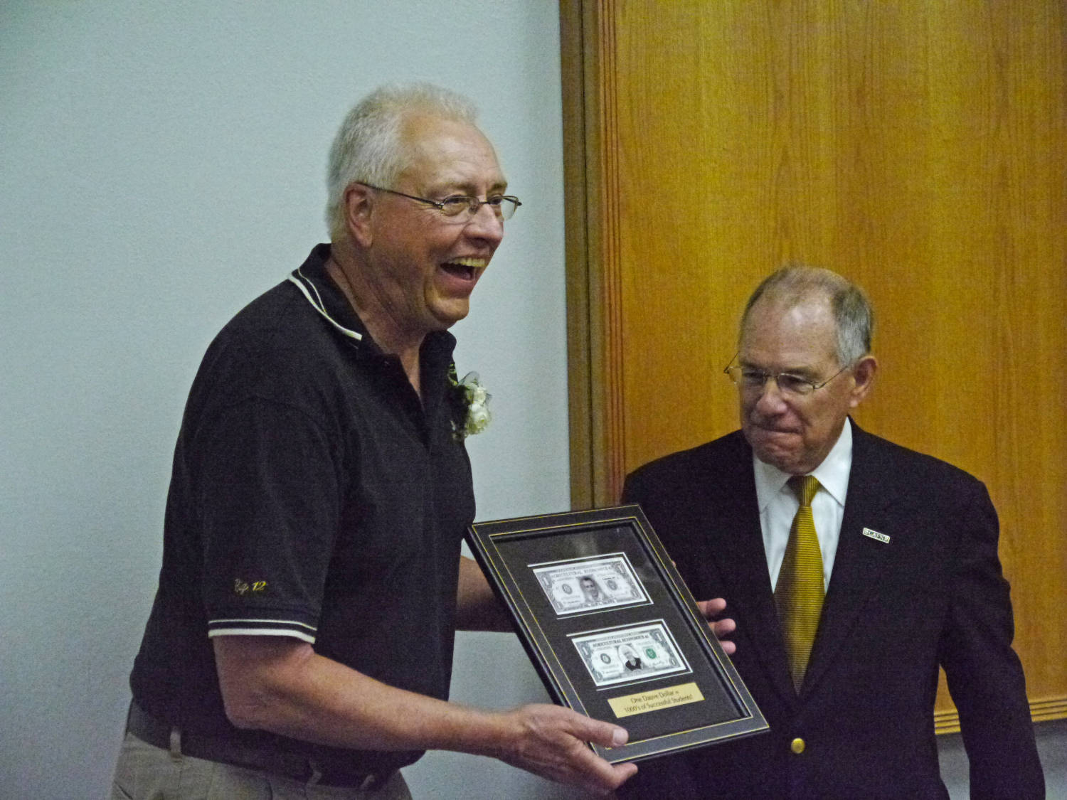 Vice Chancellor and CAFNR Dean Tom Payne presents Dauve with a framed Dauve dollar from his courses, and an updated one with a newer portrait.