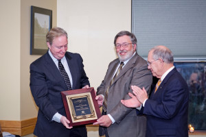 Jim Groves, associate professor, (center) presents the award to David McCaslin, as Dean Tom Payne applauds.