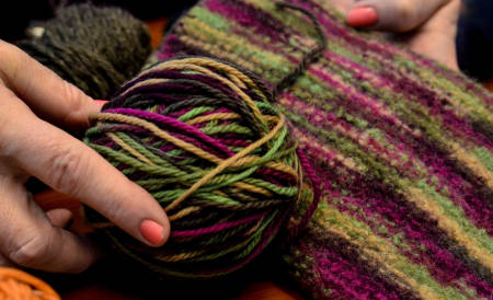 Laura shows the original yarn skein and a felted piece. Note how the colors become almost watercolor-like when felted.