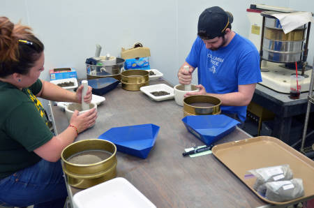 Undergraduate research assistants Megan Flatt and Michael Schoelz use pestle and mortar devices to break down soil samples into fine granules so that they can be properly tested at the Soil Health Assessment Center.