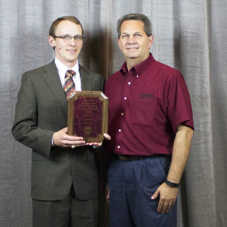 Ky Pohler, who earned his master's and doctorate degree through CAFNR's Division of Animal Sciences,  poses with the Agri-King Outstanding Animal Science Graduate Award with James Coomer, a beef and dairy nutritionist at Agri-King.