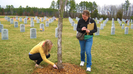 Casey Pearcy (left) and Lizzy Wernert make notes during a visit to the Missouri Veterans Cemetery in March.