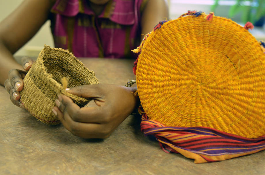 Fridah Mubichi holds a basket composed of banana plant fibers next to a traditional basket made from sisal. Photo by Stephen Schmidt.