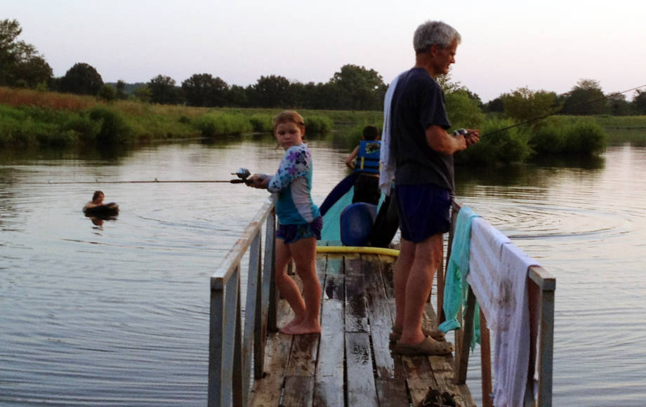 Bill Folk loves doing activities, such as fishing, with his four grandchildren. In this photo Jayna fishes with her grandfather while Cyrus jumps in and Peter hangs out in the lake. Photo courtesy of Jenn Muno.