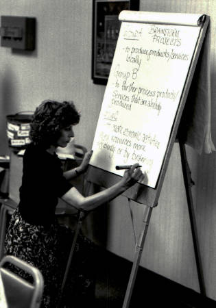 Mary Leuci writes on a flip chart during a community brainstorming session near the start of her career. Photo courtesy of Mary Leuci.
