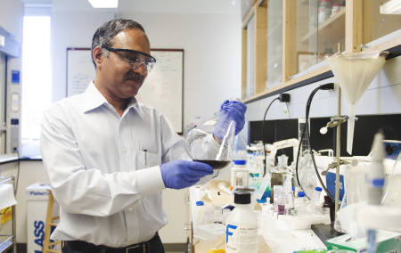 Raghu Kannan holds up a beaker containing a purple nanoparticle solution.