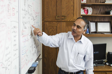 Raghu Kannan points to one of the items on a dry erase board in his office at the School of Medicine.