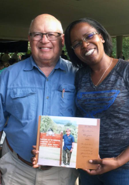 Rodney Fink and Fridah Mubichi hold a photo of when Fink was in Mubichi's hometown of Meru, Kenya, at the recent Tiger Ag Classic Steak Fry.