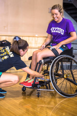 Emily Russo, a peer advisor in the Sports Management FIG, helps Elizabeth Burkett get situated in her wheelchair.