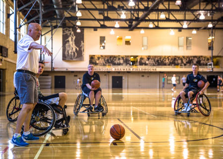 Ron Lykins, head coach of the MU wheelchair basketball program, provides instructions on how to play the game to a group of students.