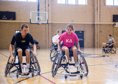 Freshman Mike Carr and Hanna Wimberly try their best to generate speed in their wheelchairs.