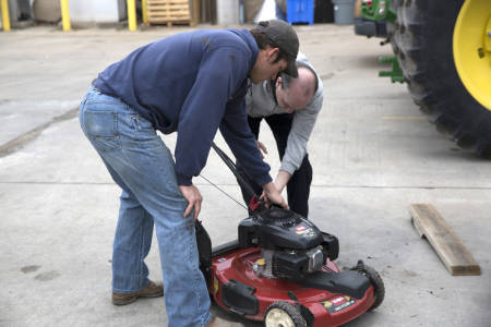 Michael Carpenter helps customer unload lawn mower