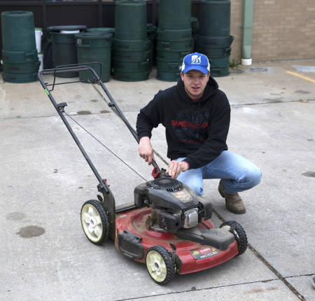 Senior Aaron Ostrander checks gas in lawn mower during drop-off.