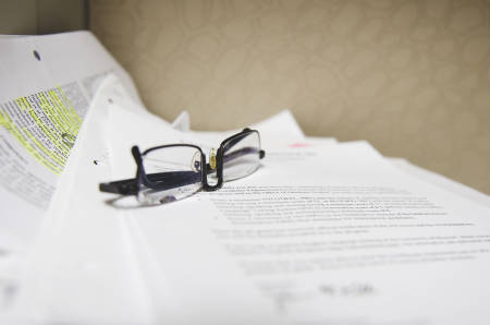 "The glasses of a scholar from Syria given the name ""John"" sits on top of academic research papers in his office."