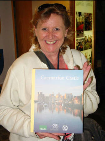 Sandy Zaring poses with a book about Caernarfon Castle in Wales. For years, she helped organize study abroad trips for the ASM department. Photo courtesy of Stephanie Sanders.
