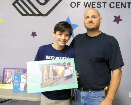 Aaron Bilbruck poses with his photovoice submission and his father, Caleb, at the photovoice reception in Sedalia May 19. Photo courtesy by Natalie Hampton.