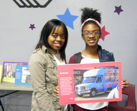 Daijah Blanch poses with her photovoice submission and his mother, Latrice Alexander, at the photovoice reception in Sedalia May 19. Photo courtesy of Natalie Hampton.