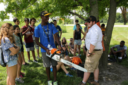 The program featured several hands-on activities, including trying to hold a chainless chainsaw.