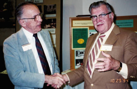 Owen Koeppe, left, shakes hands with Bob Wixom, during part of the festivities for the biochemistry department's centennial celebration in 1994. Phot courtesy of Yvonne Hill and David Wixom.