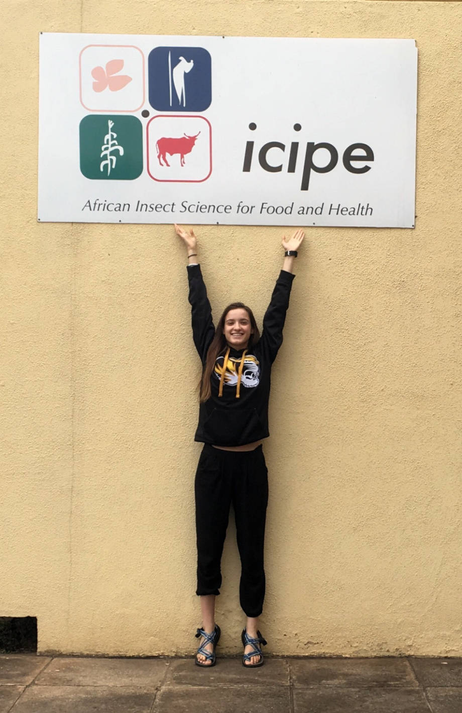 Holly Enowski stands underneath a sign at the ICIPE offices in Mbita, Kenya. Photo courtesy of Holly Enowski.