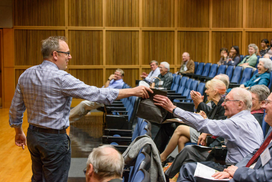 Mick Petris hands Boyd a bag during his lecture that described his current work to Boyd's research. Photo by Justin Kelley.