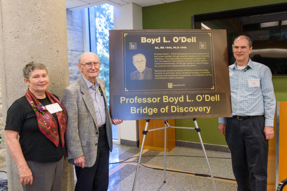 Boyd stands next to a replica of the plaque that will adorn the new Professor Boyd L. O'Dell Bridge of Discovery. He is joined by his children, Ann and David.
