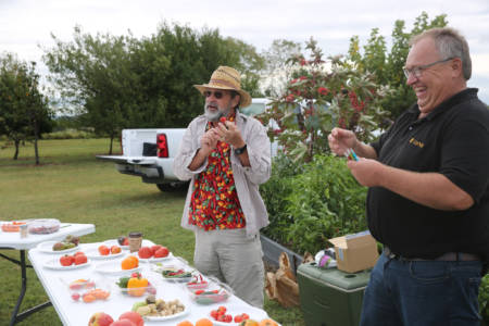 Steven Kirk (left), research specialist, and Tim Reinbott, South Farm Research Center superintendent, talk to attendees of the Southwest Research Center Field Day about tomatoes and peppers.