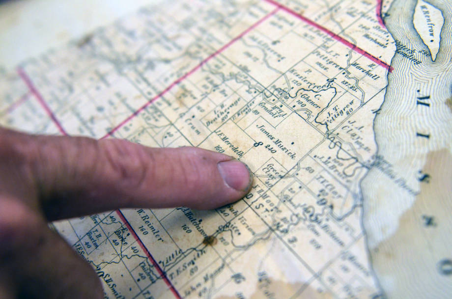 "John Clay points to the current site of his family's farm from a book that dates back to the early 1900s called the ""Standard Atlas of Moniteau County."""
