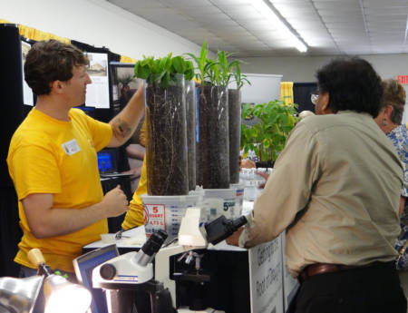 Tyler Dowd, a doctoral student being co-advised by Bob Sharp and David Braun, talk to Missouri State Fair patrons about soybean seedlings, left, and corn seedlings. The seedlings were grown in transparent tubes to reveal root development. Photo courtesy of Bob Sharp.