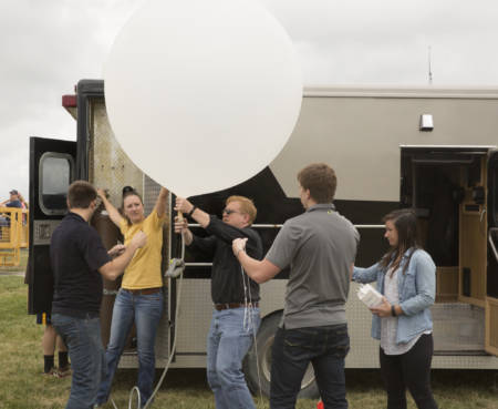 Pat Market (middle) prepares a weather balloon for launch during the South Farm Showcase.