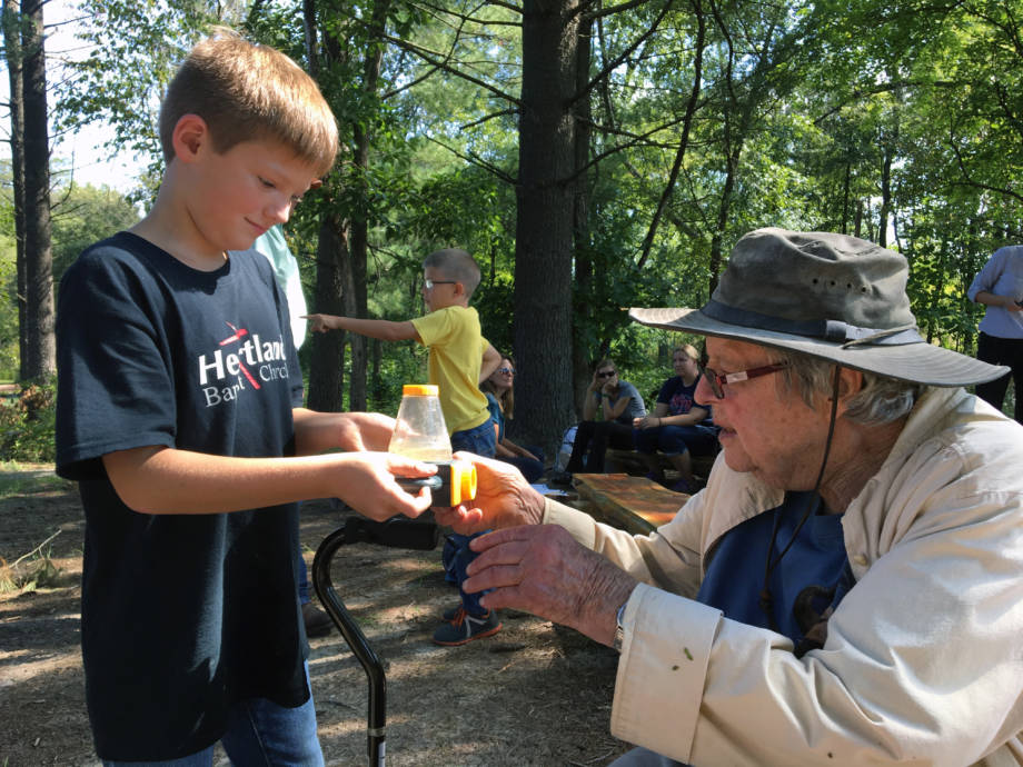 Robbie Brockman, a student at Kingdom Christian Academy, hands Pat Jones a two-way viewer that contains a tadpole that he and his classmates found.