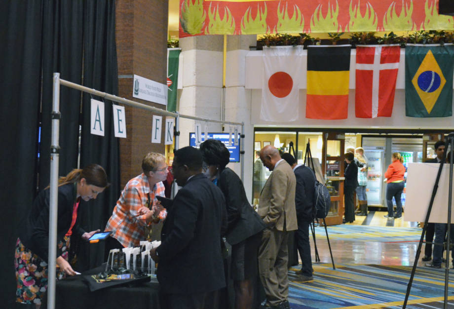 Delegates visit the registration line at the Marriott in Des Moines as flags from a few of the countries represented at the World Food Prize hang in the background.