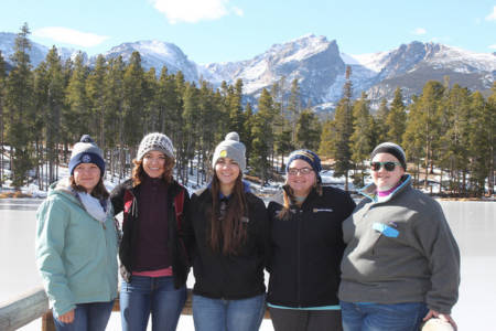 Students pose with a view of the Rockies in the background.