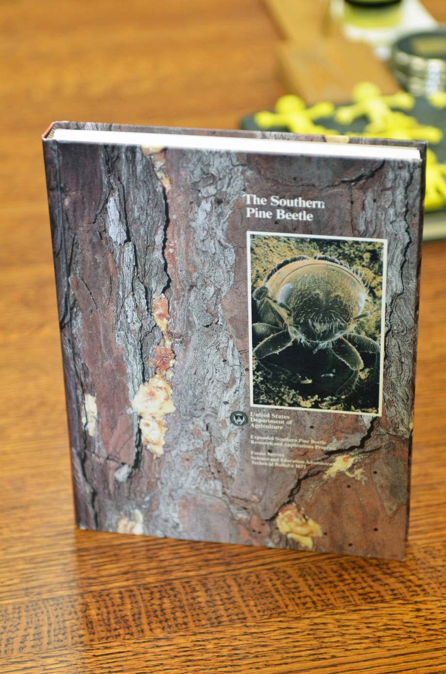 While at Texas A&M, Tom Payne serves as the research coordinator of the Southern Pine Beetle Program, sponsored by the USDA. Pictured is a book that resulted from the project's research. On the cover is a photo of a beetle that Tom took. Photo by Stephen Schmidt.