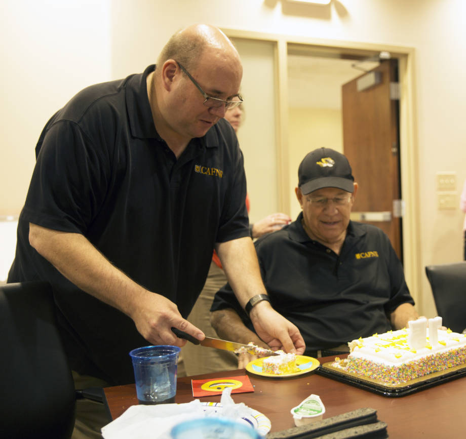James Hundle serves up the first piece of cake at the recent birthday celebration of CAFNR Dean Tom Payne. James has worked for Tom in some capacity since 1987. Photo by Aaron Duke.