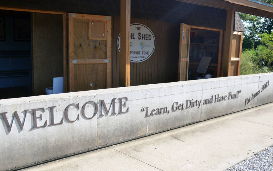 "Outside of the Soil Shed at the Prairie Fork Conservation Area a large concrete wall contains the favorite mantra of Pat Jones: ""Learn, Get Dirty and Have Fun!"""