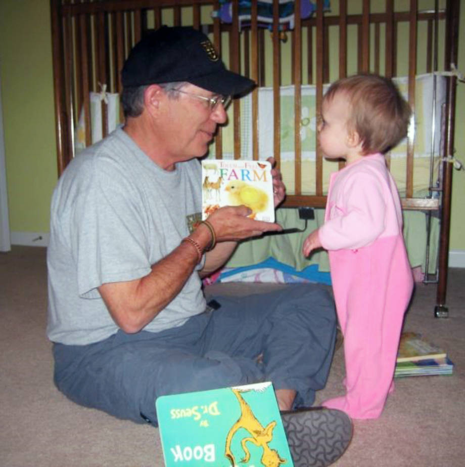 CAFNR Dean Tom Payne shows his toddler granddaugther, Caroline, who is now 11, a book about farm animals. Photo courtesy of Jacob Payne.