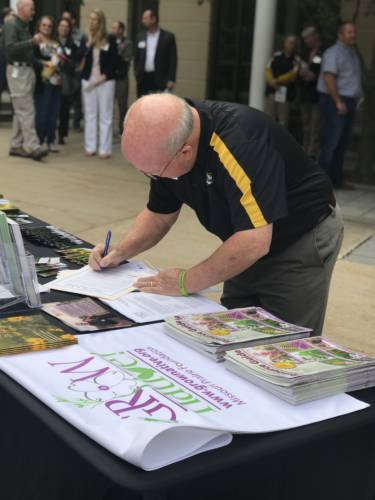 Pete Millier, Director of Campus Facilities—Landscape Services and the Mizzou Botanic Garden signs pledge to stop the spread of invasive species on MU's campus.