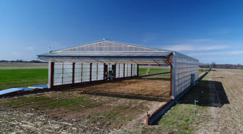 The shelters look like 50-by-100-foot greenhouses on railroad tracks. They move away from test plants when the weather is sunny and cover the plots when rain approaches, allowing the crops under the shelter to experience drought-like conditions.