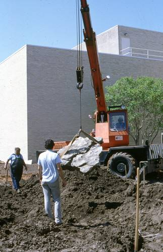 Physical Plant staff place a boulder as part of the dry creek construction.